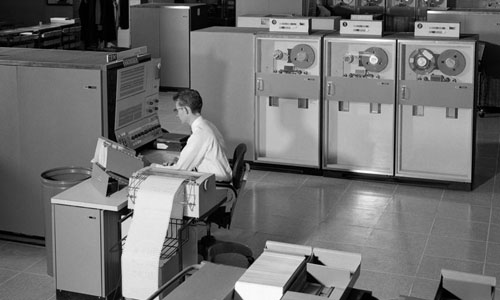 A man sitting at his desk surrounded by machines